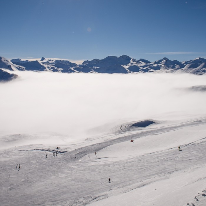 Esprit | above the clouds in Tignes with mount peaks in background