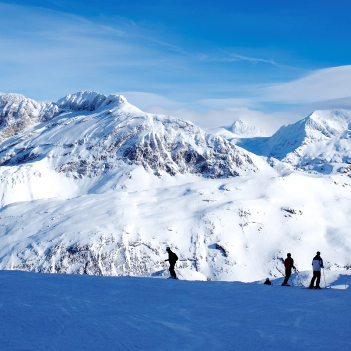 Esprit | Skiers and the surrounding mountains