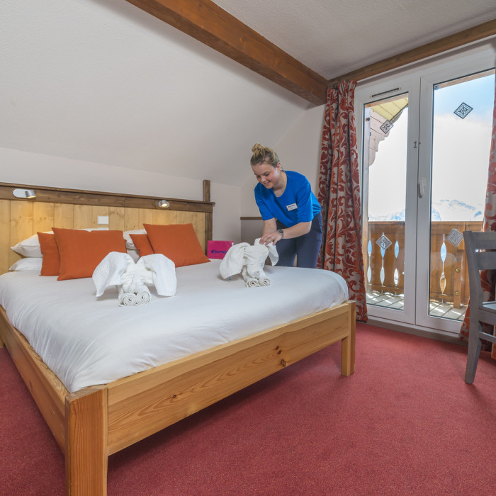 Esprit Ski | Double bedroom with staff member making the bed in the Chalet Hotel Mariandre, Alp d'Huez