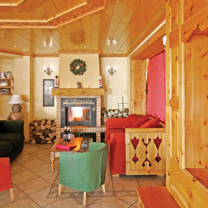 Esprit Ski | Seating area with a log fire in the Chalet Hotel Mariandre, Alp d'Huez