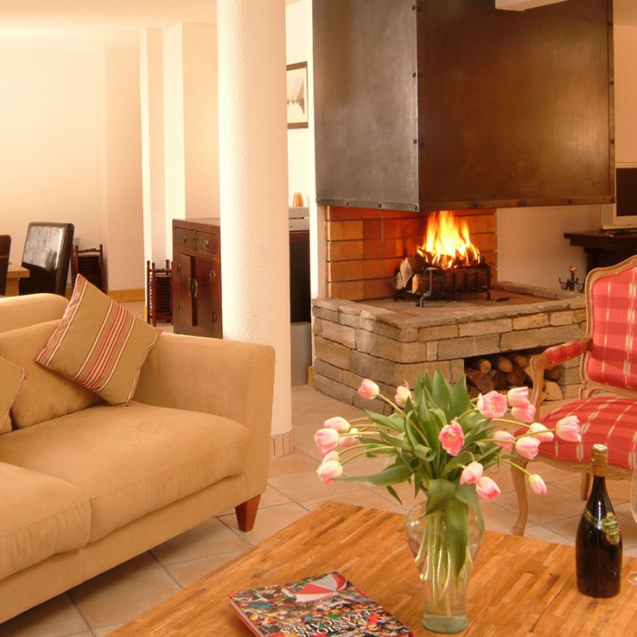 Esprit | Lounge area with open fire place in the Chalet Hermine